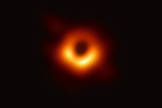 The Event Horizon Telescope (EHT) — a planet-scale array of eight ground-based radio telescopes forged through international collaboration — was designed to capture images of a black hole. In coordinated press conferences across the globe, EHT researchers revealed that they succeeded, unveiling the first direct visual evidence of the supermassive black hole in the centre of Messier 87 and its shadow. The shadow of a black hole seen here is the closest we can come to an image of the black hole itself, a completely dark object from which light cannot escape. The black hole's boundary — the event horizon from which the EHT takes its name — is around 2.5 times smaller than the shadow it casts and measures just under 40 billion km across. While this may sound large, this ring is only about 40 microarcseconds across — equivalent to measuring the length of a credit card on the surface of the Moon. Although the telescopes making up the EHT are not physically connected, they are able to synchronize their recorded data with atomic clocks — hydrogen masers — which precisely time their observations. These observations were collected at a wavelength of 1.3 mm during a 2017 global campaign. Each telescope of the EHT produced enormous amounts of data – roughly 350 terabytes per day – which was stored on high-performance helium-filled hard drives. These data were flown to highly specialised supercomputers — known as correlators — at the Max Planck Institute for Radio Astronomy and MIT Haystack Observatory to be combined. They were then painstakingly converted into an image using novel computational tools developed by the collaboration.